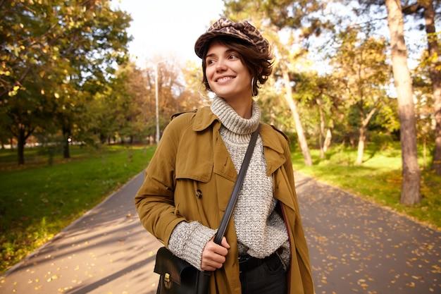 Blij dat jonge mooie bruinharige vrouw met bob kapsel positief opzij kijkt en aangenaam lacht, trendy kleding draagt tijdens het wandelen over park steegje op weekenddag