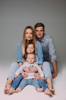 Blij dat jonge ouders poseren in de fotostudio met hun zoon en dochter en er gelukkig uitzien.