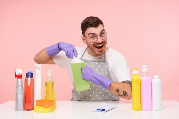 Blij dat jonge vrij kortharige brunette man in glazen gekleed in werkkleding en handschoenen gelukkig lachend tijdens het openen van fles met huishoudelijke chemicaliën, geïsoleerd op roze