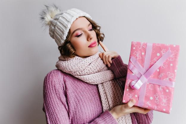 Blij dat jonge vrouw draagt gebreide witte hoed met nieuw jaar aanwezig. prachtig vrouwelijk model poseren met roze geschenkdoos versierd met schattig lint.