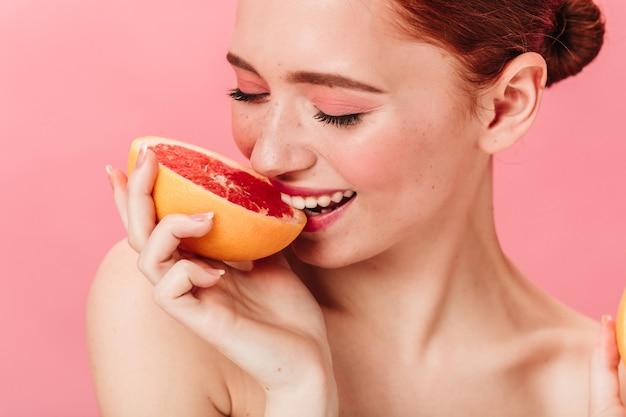 Blij dat jonge vrouw grapefruit eet. glimlachende gemberdame die van citrus op roze achtergrond geniet.