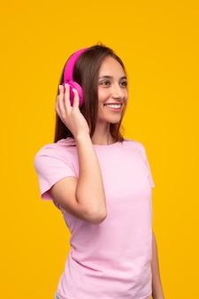 Blij dat jonge vrouw koptelefoon aanraakt en wegkijkt met een glimlach terwijl je naar muziek luistert tegen een gele achtergrond