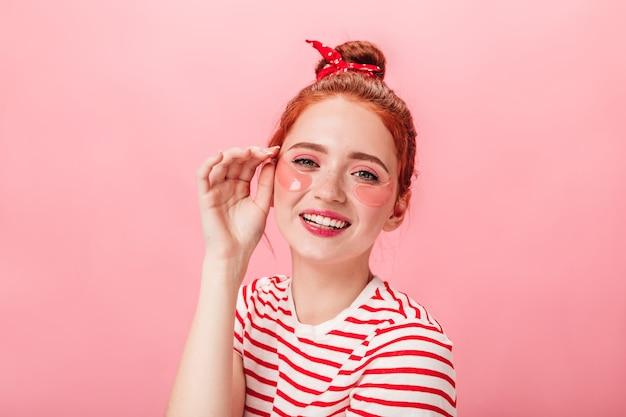 Blij dat jonge vrouw met ooglapjes camera bekijkt. studio shot van opgewonden gember meisje doet huidverzorgingsbehandeling op roze achtergrond.