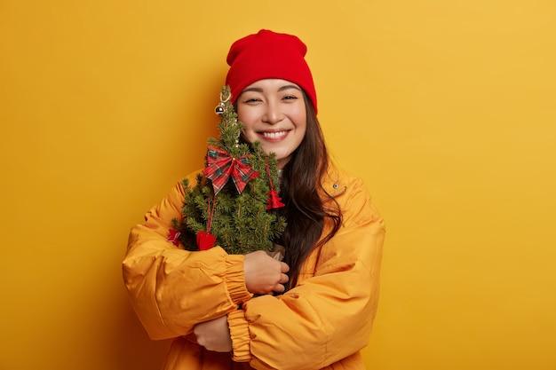 Blij dat koreaanse vrouw in rode hoed en geel jasje kleine groen versierde nieuwjaarsboom omarmt, zacht glimlacht, feeststemming heeft, geïsoleerd op gele achtergrond.