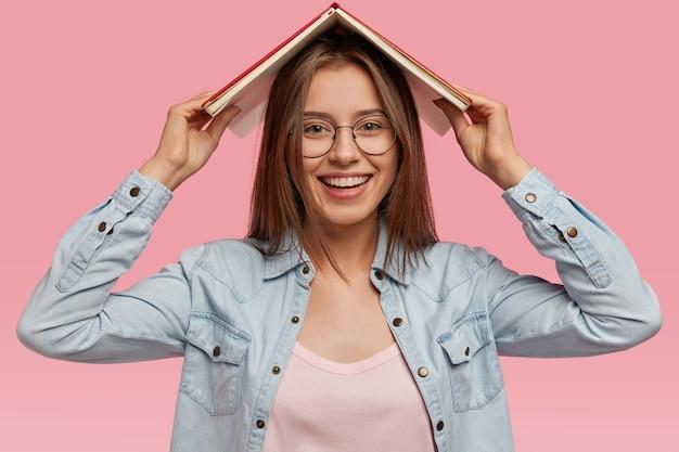 Blij dat mooie jonge vrouw een boek over het hoofd draagt, lacht zachtjes, geniet van het lezen van interessant verhaal, draagt stijlvolle kleding, modellen tegen roze muur, voelt plezier van haar favoriete hobby