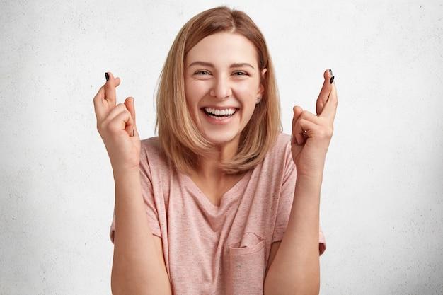 Blij dat mooie jonge vrouwelijke student gelukkig naar de camera kijkt en vingers kruist, heeft een groot verlangen om examen met succes af te leggen, geïsoleerd over witte betonnen muur.