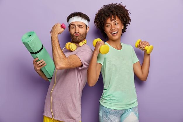 Blij dat multi-etnische man en vrouw naar het sportcentrum gaan, trainen met halters, fitnessmat vasthouden, tegen elkaar staan, grappige blikken hebben, t-shirts dragen, geïsoleerd op paarse muur