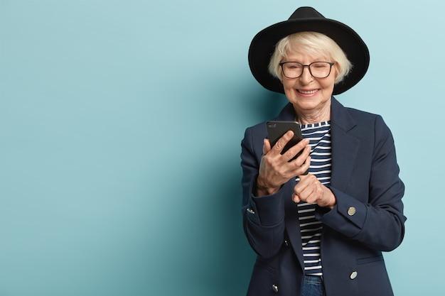 Blij dat oude vrouw goed nieuws ontvangt op slimme telefoon, feedback geeft, modieuze zwarte hoed draagt