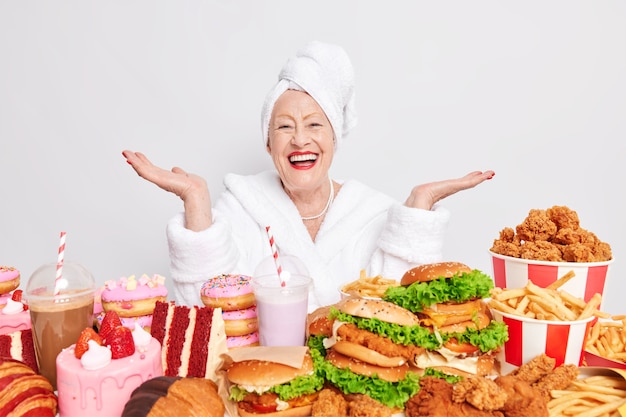 Blij dat oudere dame haar handpalmen spreidt, voelt zich gelukkig heeft ongezonde onevenwichtige voeding eet junkfood