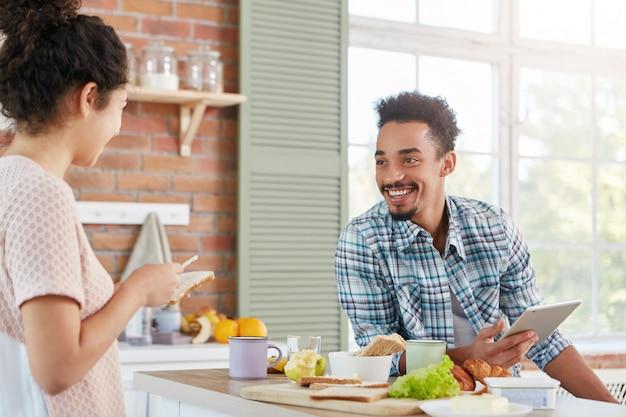 Blij dat positieve hipster kerel nonchalant gekleed, zit aan tafel, wacht op lunch bereid door huisvrouw, houdt digitale tablet,
