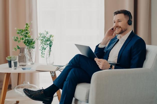 Blij dat professionele mannelijke werknemer die zich bezighoudt met online conferentie, laptopcomputerheadset gebruikt, heeft een gelukkige meningsuiting en heeft communicatie op afstand met zakelijke partners die webinars kijken. man coach indoor