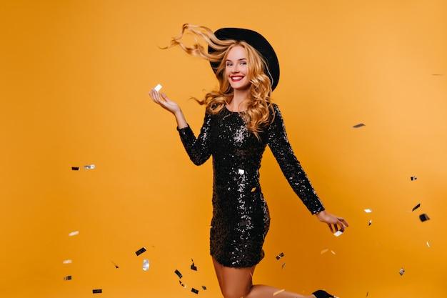 Blij dat slank meisje in zwarte jurk poseren onder confetti. betoverende langharige vrouw die op gele muur bij partij danst.