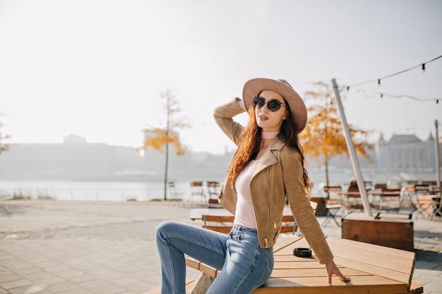 Blij dat slanke vrouw in spijkerbroek op houten tafel in straatrestaurant zit