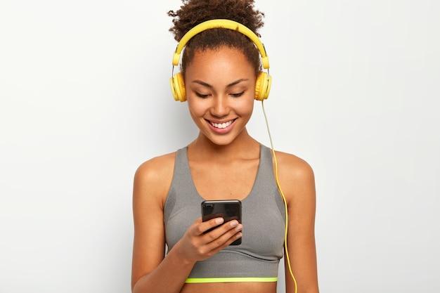 Blij dat sportieve krullende afro-amerikaanse vrouw luistert naar muziek in de koptelefoon, breed lacht, sportbeha draagt.