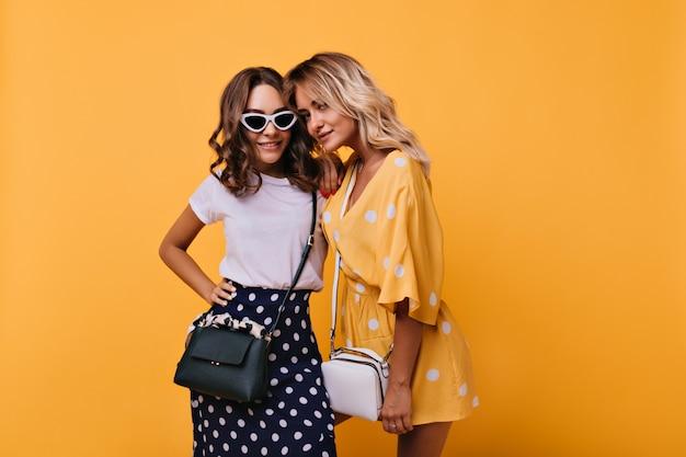 Blij dat stijlvolle vrouw in zonnebril permanent in zelfverzekerde pose. optimistische jonge dames poseren met een glimlach op geel.