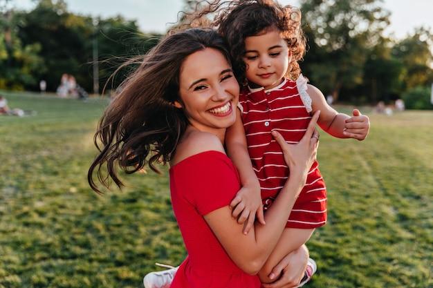 Blij dat vrouw haar dochter vasthoudt en naar de camera lacht. buiten foto van emotionele jonge moeder ontspannen in weekend met kind.