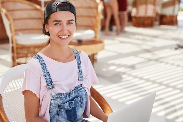 Blij dat vrouwelijke freelancer in stijlvolle kleding, werkt op draagbare laptopcomputer