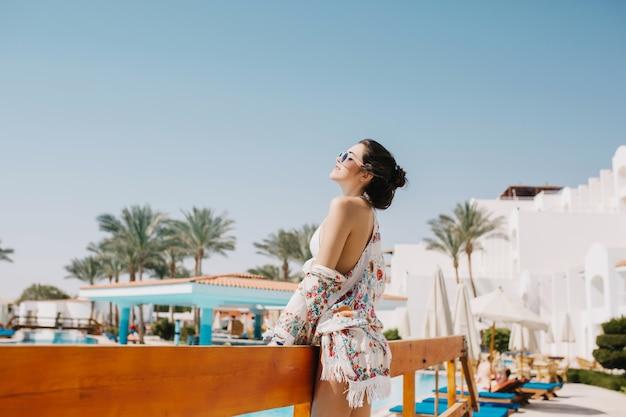 Blij donkerharig meisje in witte kledij die van frisse zeelucht genieten die zich voor hotel bevinden. portret van dromerige stijlvolle jonge vrouw poseren buiten tijdens het rusten op resort met palmbomen