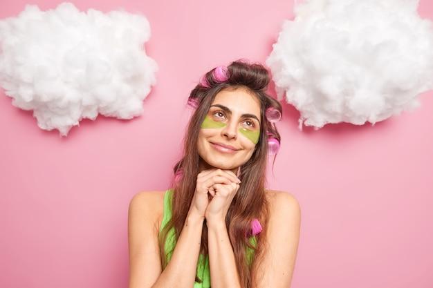 Blij dromerige brunette vrouw houdt handen onder de kin past groene collageen patches toe, past haarrollers toe voor het maken van kapsel geïsoleerd over roze muur witte wolken erboven