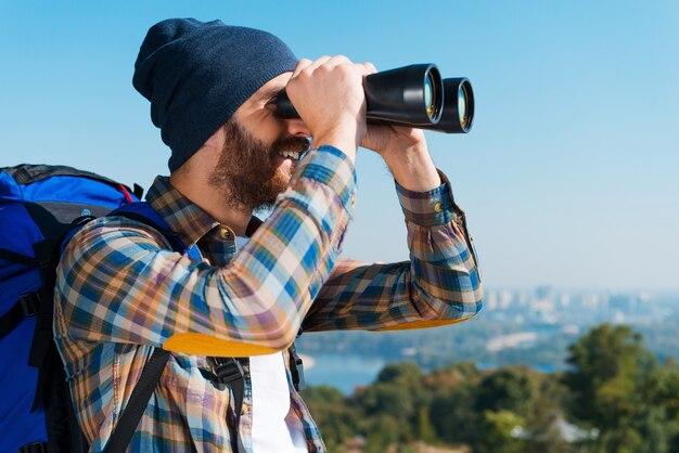 Blij een ontdekkingsreiziger te zijn. knappe jonge bebaarde man die rugzak draagt en door een verrekijker wegkijkt met een glimlach
