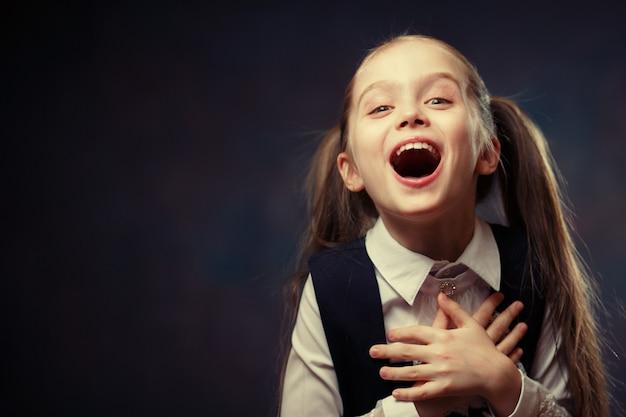 Blij elementair schoolmeisje emotioneel portret.