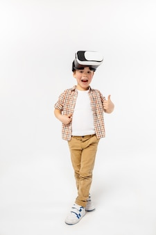Blij en benieuwd. kleine jongen of kind in spijkerbroek en shirt met virtual reality headset bril geïsoleerd op witte studio achtergrond. concept van geavanceerde technologie, videogames, innovatie.