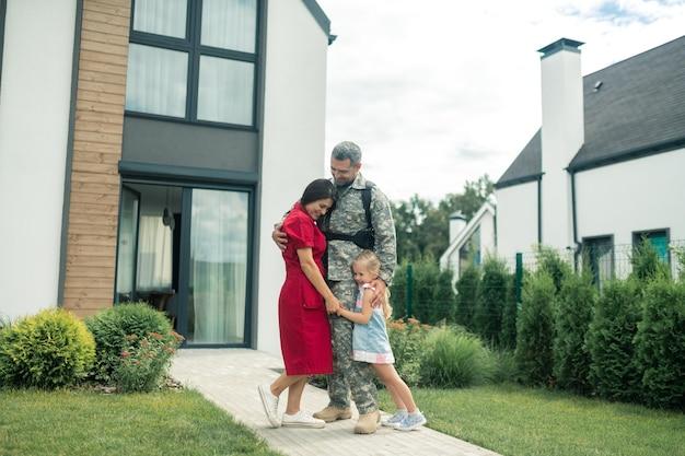 Blij en emotioneel. familie voelt zich gelukkig en emotioneel nadat vader thuiskomt van militaire dienst