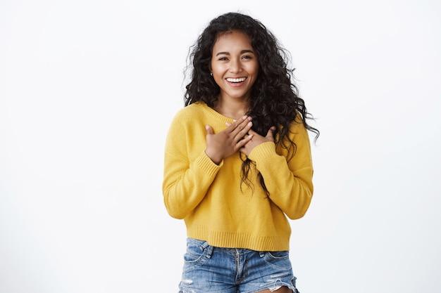 Blij en gevleid schattig lachend meisje met krullend haar, draag een gele, gezellige trui, druk de handen op de borst, voel me dankbaar, bedankt voor hulp, grijnzend waarderen mooi cadeau