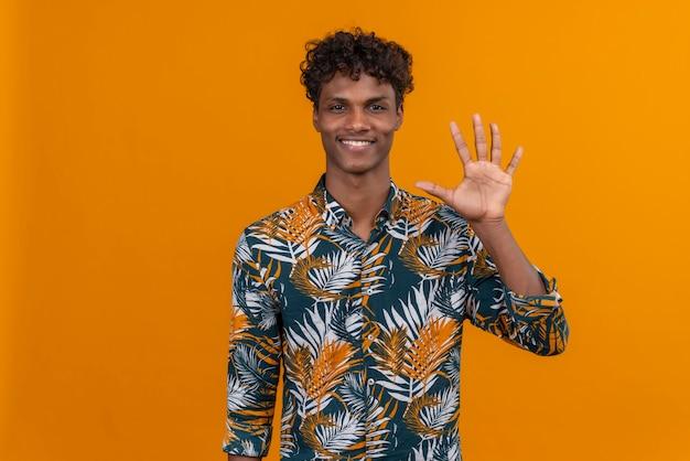 Blij en glimlachende jonge knappe donkere man met krullend haar in een shirt met bladerenprint terwijl hij met vingers nummer vijf laat zien