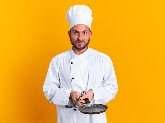 Blij en onder de indruk jonge blanke mannelijke kok in uniform van de chef-kok en dop met spatel en koekenpan kijken camera geïsoleerd op oranje muur met kopie ruimte