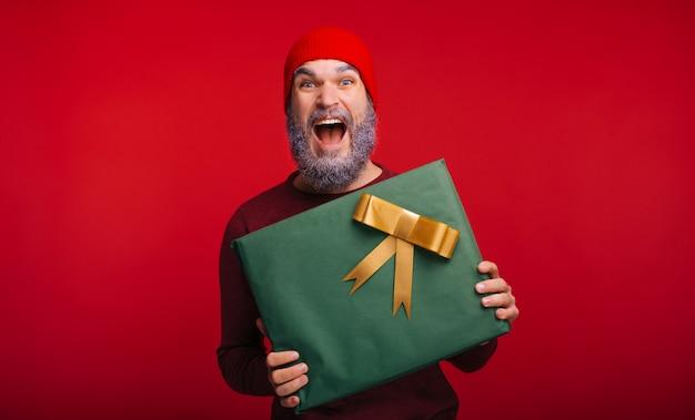 Blij en opgewonden bebaarde man heeft zojuist een geschenk gekregen van de kerstman