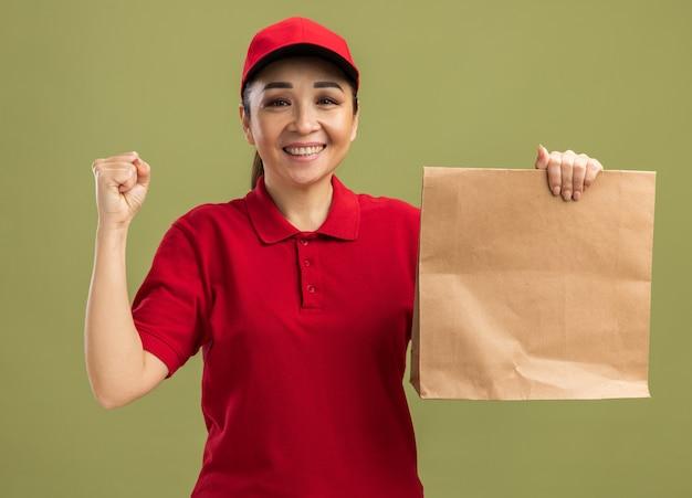 Blij en opgewonden jonge bezorger in rood uniform en pet met papieren pakket met glimlach op gezicht balde vuist over groene muur