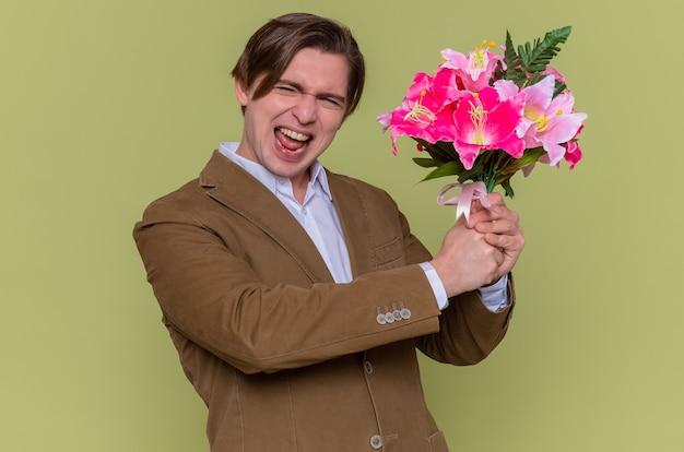 Blij en opgewonden jonge man met boeket bloemen