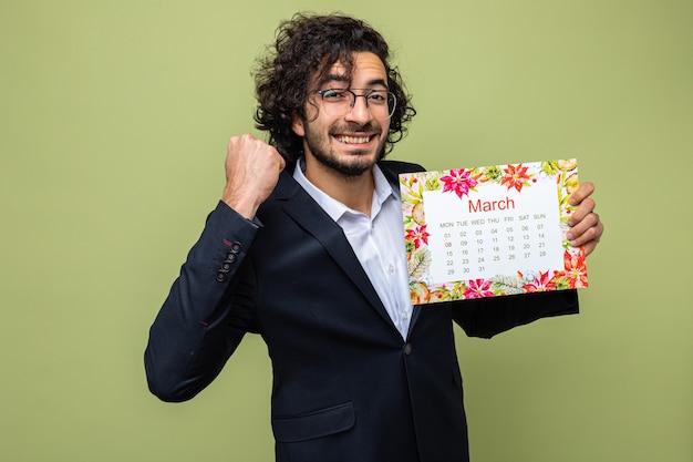 Blij en opgewonden knappe man in pak met papieren kalender van de maand maart