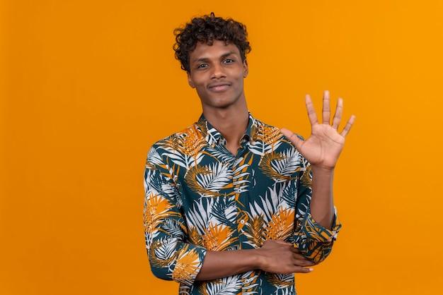 Blij en positief jonge knappe donkere man met krullend haar in bladeren bedrukt overhemd terwijl hij met vingers nummer vijf laat zien