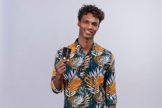 Blij en tevreden jonge knappe donkere man met krullend haar in bladeren bedrukt overhemd en creditcard tonen