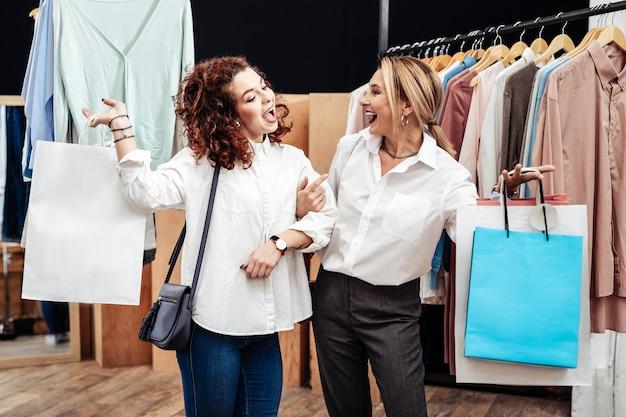 Blij en tevreden. knappe vrolijke moeder en dochter voelen zich gelukkig en tevreden bij het verlaten van de winkel met tassen
