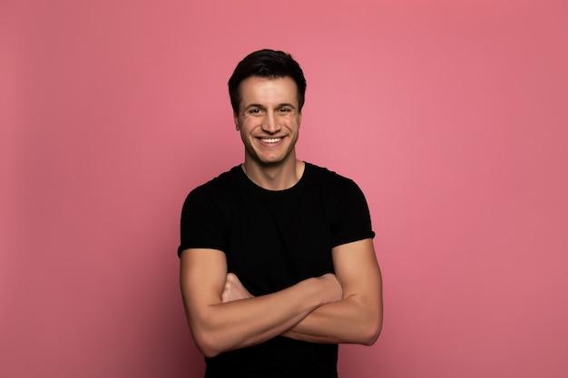 Blij en trots. knappe jongeman in een zwart t-shirt, die met gevouwen armen staat en oprecht glimlacht.