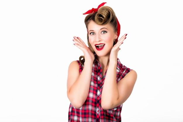 Blij en verras mooie jonge vrouw met pin-up make-up en kapsel