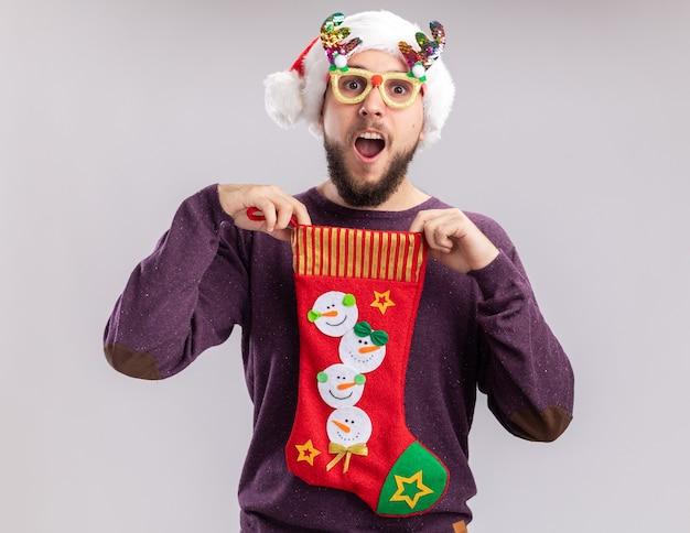 Blij en verrast jonge man in paarse trui en kerstmuts met grappige bril met een kerstsok kijken camera glimlachend staande op witte achtergrond