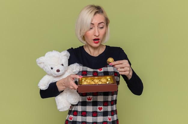 Blij en verrast jonge vrouw in de mooie teddybeer van de kledingsholding