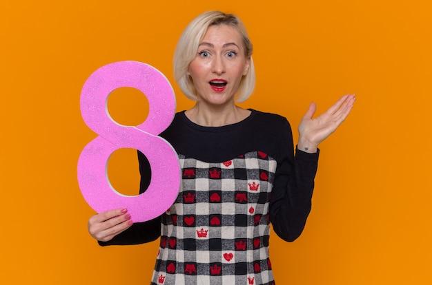 Blij en verrast jonge vrouw met nummer acht gemaakt van karton