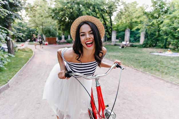 Blij gelooid meisje in zomerhoed geluk uitdrukken tijdens rit in park. buiten schot van schattige brunette vrouw in rok poseren met fiets op aard.