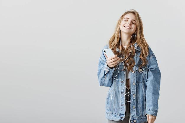 Blij gelukkig blond meisje genieten van geweldig nieuw lied in oortelefoons, muziek luisteren, smartphone houden