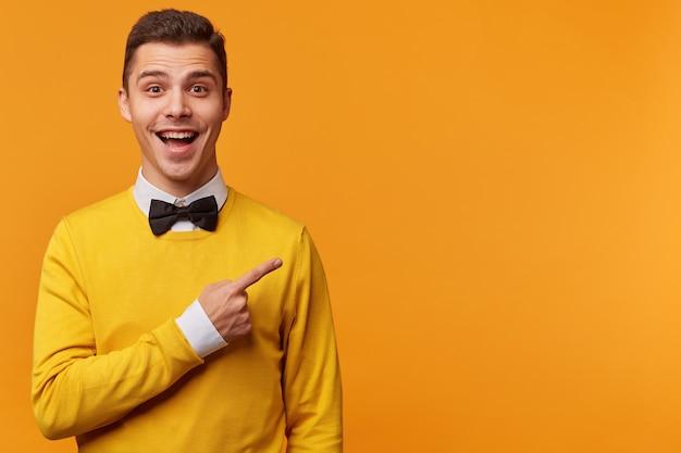 Blij gelukkig man in gele trui over wit overhemd en zwarte vlinderdas naar rechts wijzend met zijn vinger