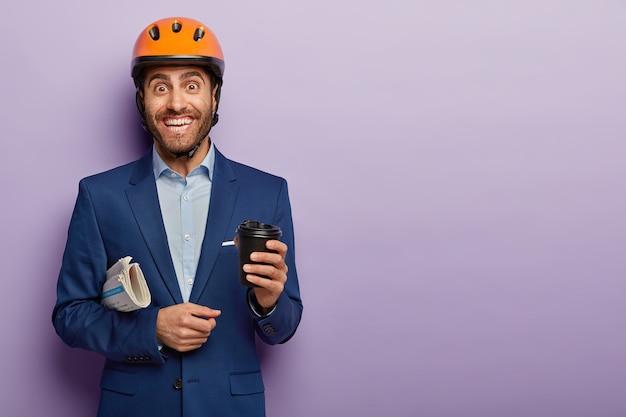 Blij gelukkig mannelijke bouwvakker heeft koffiepauze na het werk, draagt een veiligheidshelm en een elegant pak, glimlacht positief
