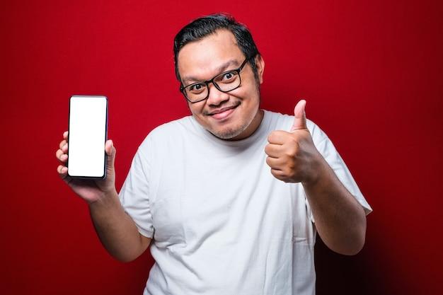 Blij gelukkige jonge aziatische man in wit t-shirt glimlachend naar camera terwijl smartphone wijzend op mobiel scherm over rode achtergrond