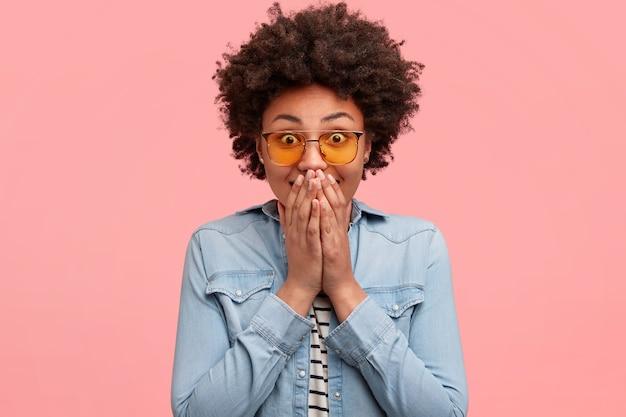 Blij, gelukkige jonge vrouw heeft uitdrukking verbaasd, bedekt mond met beide handen, heeft vreugdevolle uitdrukking, geïsoleerd over roze muur