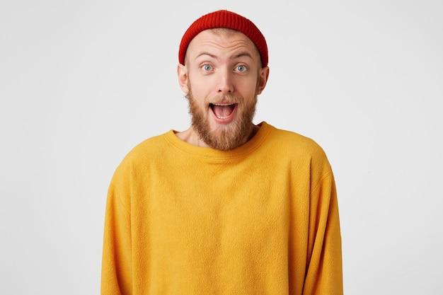 Blij gember-gepaneerde man met blij verbaasde uitdrukking, draagt een rode hoed en casual trui, verheugt zich met succes gemaakt project