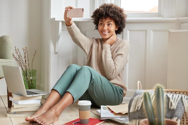Blij gemengd ras vrouw met afro kapsel, vormt op mobiele telefoon voor het maken van selfie